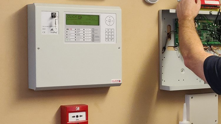 Click 24's engineer updating and maintaining a fire alarm system